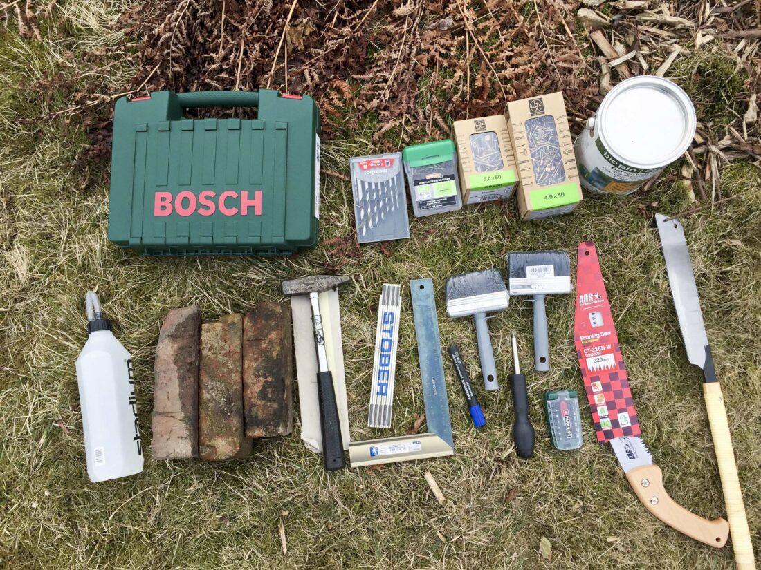 Werkzeuge, um eine Beeteinfassung aus Holz selber zu bauen: Säge, Bohrschrauber, Bohrer, Torxschrauben, Hammer, Anschlagswinkel, Farbe, Pinsel.