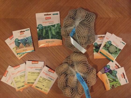 Saatgut von Bingenheimer – plus Saatkartoffeln von Biogartenversand – liegen auf einem Küchentisch aus Holz.