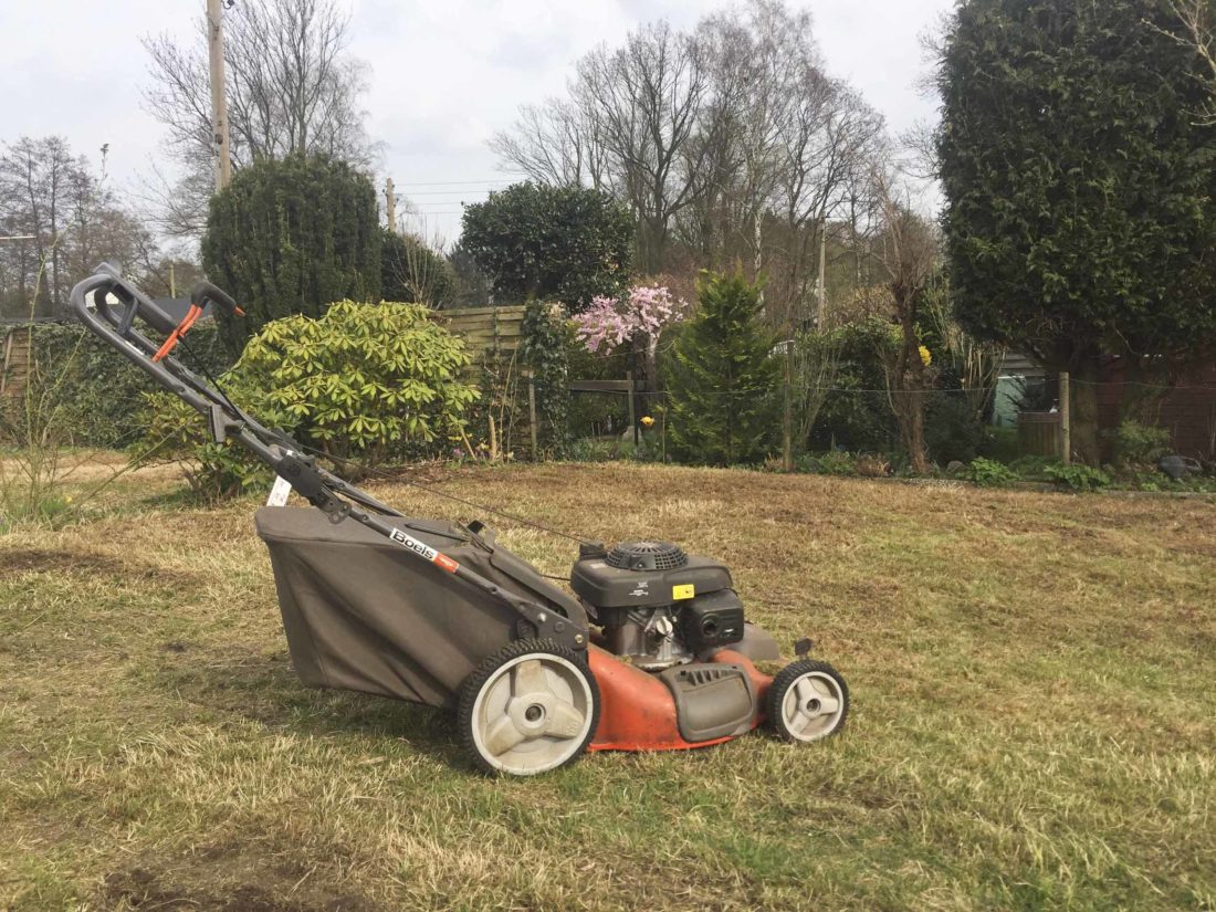 Ein orangefarbener Rasenmäher steht auf einer Rasenfläche.