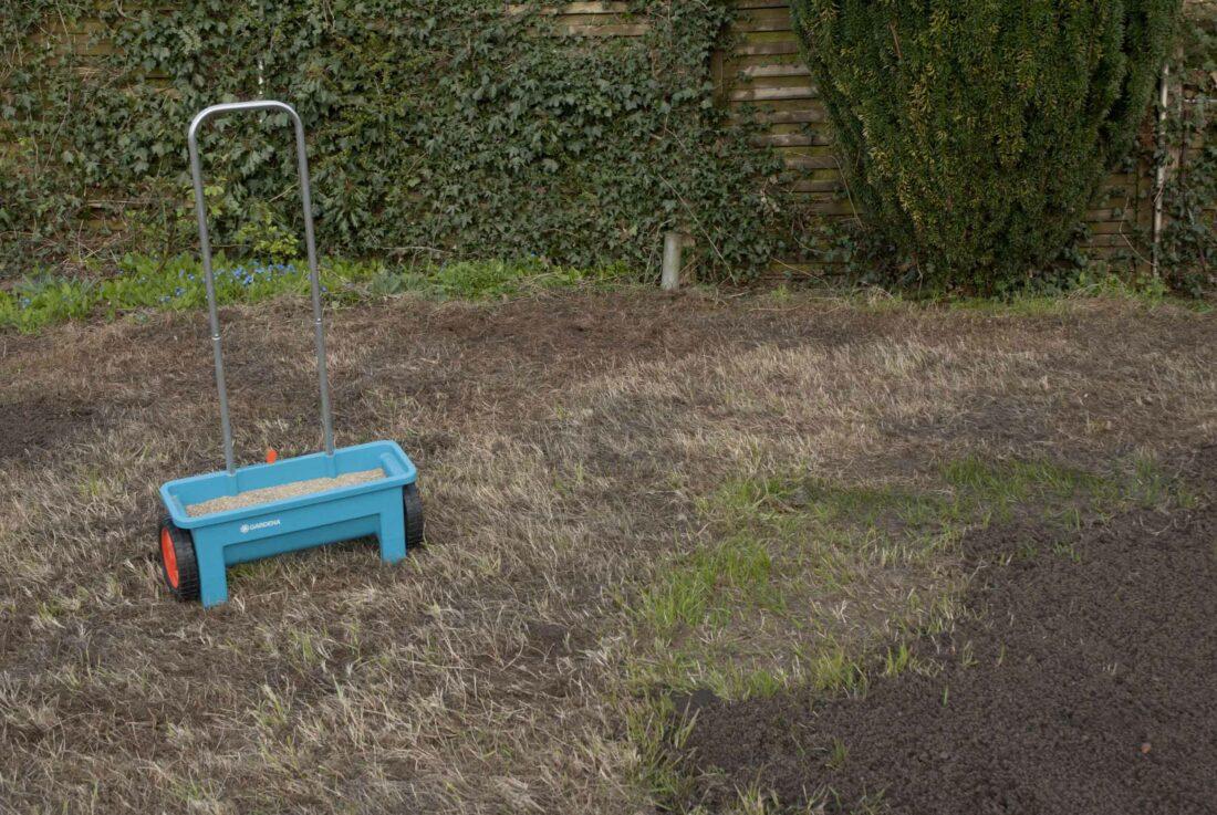Ein Saatwagen steht auf einem braunen Rasen.