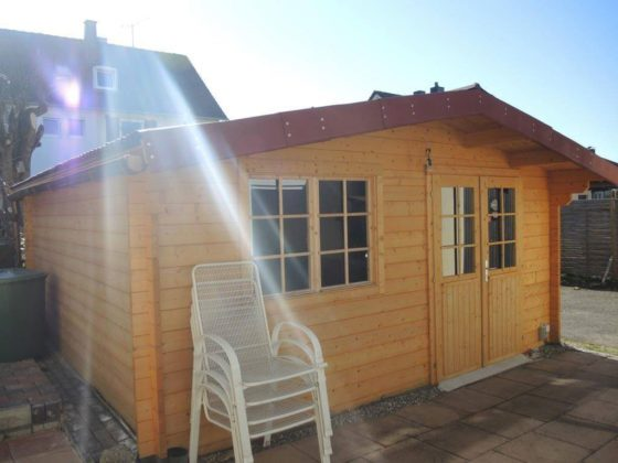 Gartenhaus versetzen: Ansicht einer Gartenhütte aus Holz von vorne, davor stapeln sich weiße Gartenstühle.