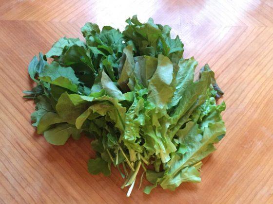 Verschiedene Salatblätter liegen auf einem Küchentisch aus Holz.