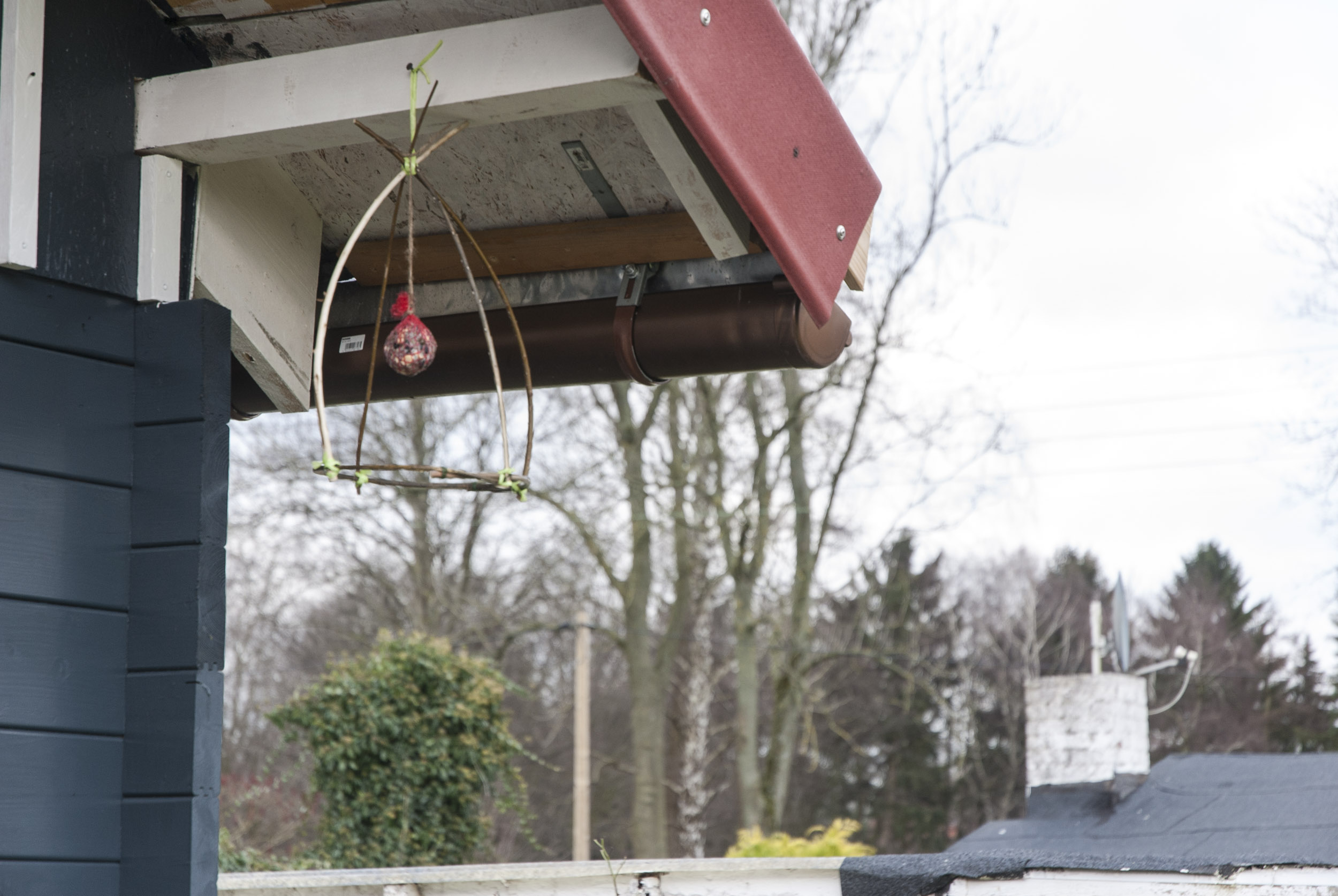 Eine DIY-Vogelfutterstelle aus Zweigen hängt an einem Dachvorstand einer Holzhütte, in der Mitte ist ein Meisenknödel befestigt – eine von vielen Ideen für Garten-Geschenke.