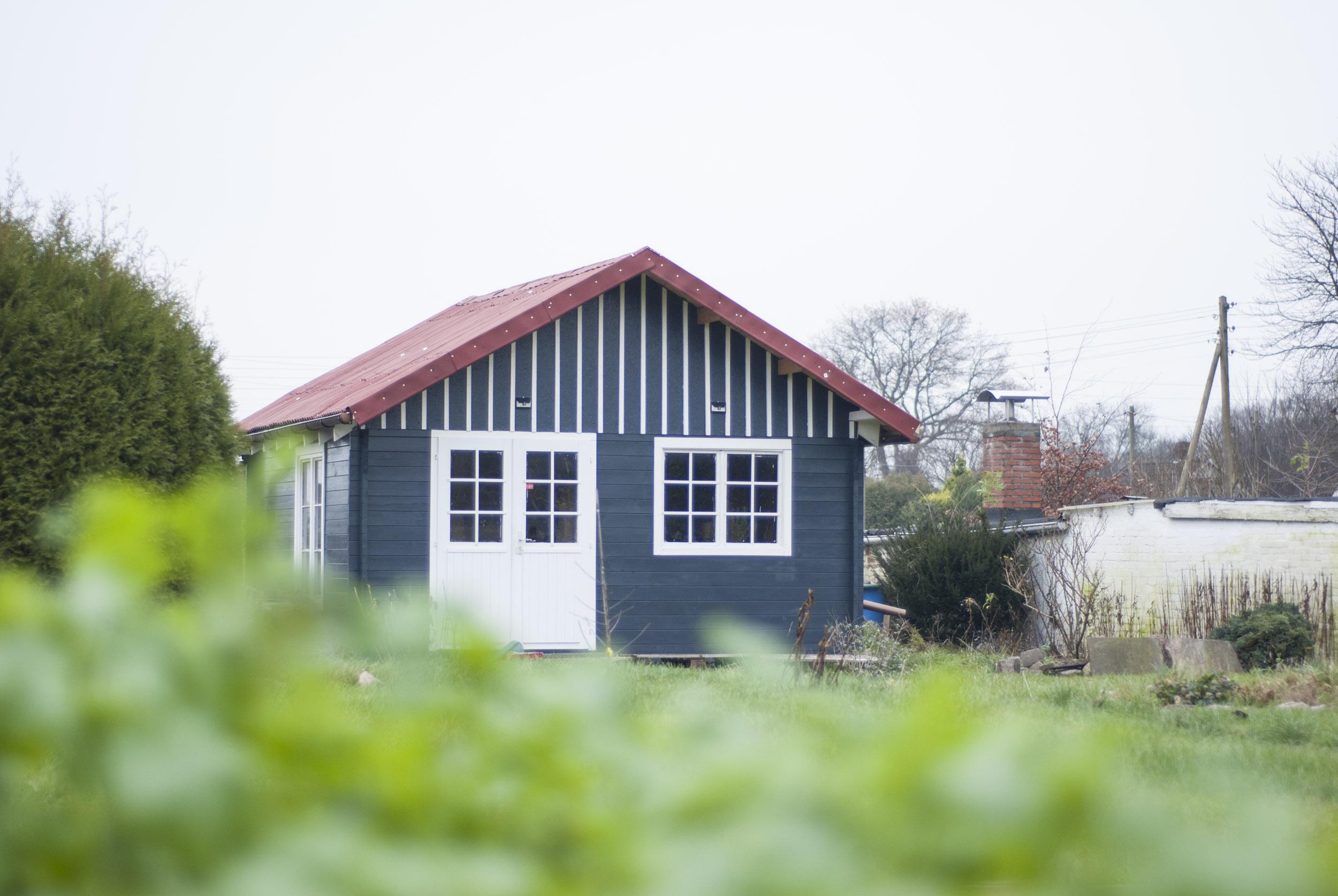 Blick auf eine Anthrazit-farbene Gartenhütte mit rotem Dach und weißen Giebellatten.