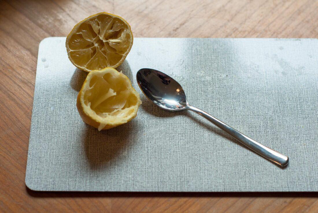 Zwei Zitronenhälften liegen auf einem Brettchen, daneben liegt ein Löffel.