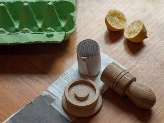Anzucht: Ein Eierkarton liegt neben zwei Zitronenhälften auf einem Esstisch, im Vordergrund ist ein PaperPotter auf eine Stück Zeitungspapier zu sehen.