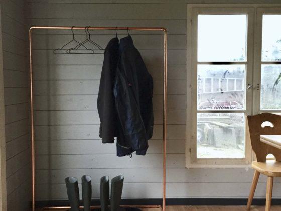 Eine DIY-Kleiderstange steht in einem Raum einer Gartenhütte.