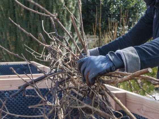 Hochbeet befüllen: Zwei behandschuhte Hände werfen mehre Äste und Zweige in ein selbst gebautes Hochbeet.